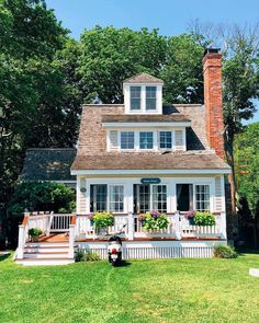 Charming farmhouse complete with a partial wraparound porch, a beautiful red brick chimney, and gorgeous summer flower boxes.