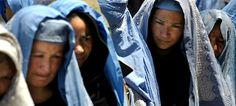 Afghan widows line up to receive food rations at a CARE International food distribution center in Kabul © AP 2005