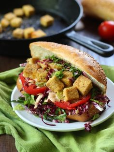 Tofu cubes are coated in Cajun seasoned cornmeal, pan-fried to a crisp, and stuffed into crusty rolls with veggies and vegan remoulade sauce to make these mouthwatering tofu po' boy sandwiches.