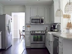 This late 1980s kitchen is updated by painting the oak cabinets a soft warm gray, refinishing the hardwood floors and installing granite countertops, a new apron-front sink, a bridge faucet, wire pendant lights and stainless steel appliances. For a distinct look, an unconventional size of subway tile (2x8) with dark gray grout is ... more