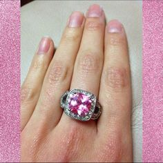 Pretty in Pink CZ Fashion Ring Super glitzy and glam pink Cubic Zirconia fashion ring. Pink center CZ stone is so fiery, casts rainbows and beautiful lights everywhere you go! White accent CZ stones provide a glamorous and striking frame. Great condition. Only flaws: some VERY slight tarnishing on back of band & some light scratching on the band. Very slight. Both pictured in third photo, top right and left frames.  Free with any purchase of $10 and higher. Jewelry Rings
