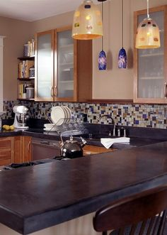 Stained concrete countertops provide a contemporary edge.   Like the mosaic glass tile backsplash (but not the color).