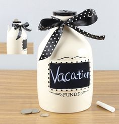 Our Money Jar Coin Bank with Chalkboard allows you to customize your savings goals. Whether saving for a Vacation or maybe a Vegas trip you can easily change and update your saving goals.  The ceramic Money Bottle has a high-gloss finish and is decorated with a fabric bow.  The chalkboard on the Money Jar is embossed with a decorative trim.  Deposit your bills and coins through the handy slot on the cap.  Retrieve your savings through the door on the bottom of the jar.