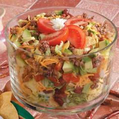 Taco Bean Salad Recipe 3 large tomatoes 1 head iceberg lettuce, torn 6 cups coarsely crushed tortilla chips 2 cups (8 ounces) shredded cheddar cheese 1 can (16 ounces) kidney beans, rinsed and drained 1 large ripe avocado, peeled and chopped 2 cups Seasoned Hamburger Mix, thawed 1 bottle (7 ounces) green taco sauce 4 green onions, chopped Ranch salad dressing or dressing of your choice