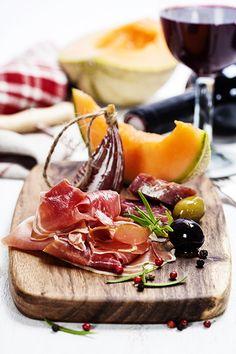 Italian cuisine. Antipasto. Prosciutto, melon, salami, olives and wine - Italian cuisine. Antipasto. Prosciutto, melon, salami, olives and wine