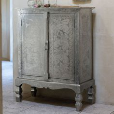 Shine meets strength in this Lotus Collection German Silver Armoire by Roost. Hardwood cabinets are clad by hand with beautiful hand-etched sheets of German silver- a silver-colored blend of copper, zinc and nickel. This Roost Lotus Cabinet opens to two shelves and is finished in dark-stained wood.