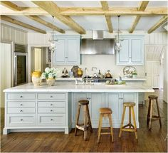 Incredible country kitchen with rustic wood beams ceiling and gray wood panel walls set the stage for beautiful blue kitchen cabinets flanking an incredible barrel kitchen hood.