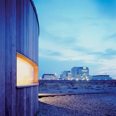 A timber-clad house built around a nineteenth-century railway carriage on Dungeness beach in Kent, England.