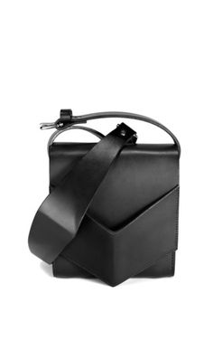 The Sculpted Shoulder Bag is made from smooth saddlery leather and features a raised cuff detailing that conceals a sam browne closure. The bag has a sculpted strap that is fully adjustable using its two buckles, and can be worn off the shoulder or across the body by reversing the strap. Handmade in London. Please note: This item is available for full credit or refund.