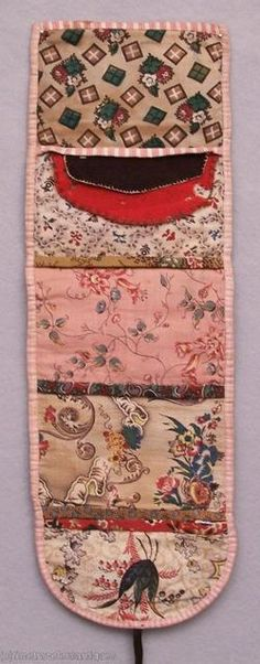 "One of the finest & earliest examples of an American housewife. Circa 1830 roll up - 14"" x 4-1/2"", all hand sewn, five interior pockets, each with different calico print, each bound with various calicos, two wool needle flaps, black ties, bound in pink checked cotton and early calico print on exterior. De-accessioned from a New York state museum.  (Modeled my own housewife on this one.)"