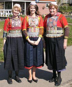 """Marker klederdracht. Vrouw in het midden in de """"wilde kleuren"""" niet in de rouw dus en de vrouwen links en rechts zijn wel in de rouw. Dat is te zien onder andere aan de groene wol waar de rode baai mee is afgezet."""