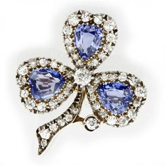 A late Victorian sapphire and diamond clover leaf brooch, the three leaves each set with a heart-shaped faceted sapphire, set to the centre of a cluster surround of old-cut diamonds, to a diamond-encrusted stalk, the sapphires estimated to weigh a total of 3.4 carats, the diamonds estimated to weigh a total of 1.4 carats, set in silver to a yellow gold mount and brooch fitting, gross weight 6.7 grams, circa 1890.