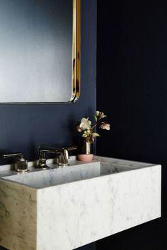 Une salle de bain au mur bleu foncé miroir en laiton et vasque en marbre blanc gris minimaliste.