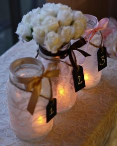 Lace mason jars with candles, and flowers for centerpieces. I like this for the other tables with out flowers. Hmm may be to many mason jars