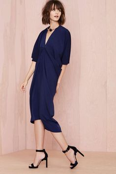 This kimono-inspired navy dress features a V neckline, dolman sleeves, and a tapered fit.