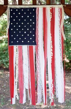 Patriotic Ribbon, Lace & Fabric Scrap Flag DIY: Use torn fabric to create this dangling flag. Choose unique fabrics and fun buttons as stars for an extra decorative touch. Click through for the full DIY instructions and for more easy 4th of July decorations you can make at home.