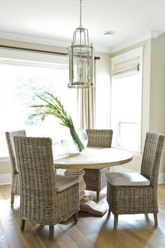 Sun filled dining room boasts a glass and nickel lantern illuminating a round salvaged wood dining table lined with wicker dining chairs placed in front of a large picture window dressed in beige drapes.