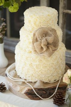 Adorable two-tiered wedding cake with a burlap bow #wedding #weddingcake #rustic #farmhouse #burlap