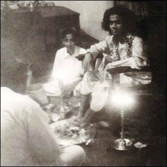 A rare photograph of Bhagavan Baba as a teenage boy, allowing a devotee to perform Pooja at his Lotus Feet.
