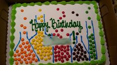 """Science birthday cake using skittles.  Had club store make cake (with borders and happy birthday slogan).  I added test tubes and beakers with gel frosting tube from grocery store.  """"filled"""" them with skittles to look like bubbling liquids."""