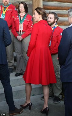 The Duchess of Cambridge. Catherine Red coat, Hair worn back, earrings. Back or rear view of red coat. pump heels shoes.