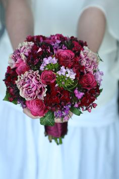 Bouquet of sweet william, dianthus, roses and ivy trails in reds and pinks.