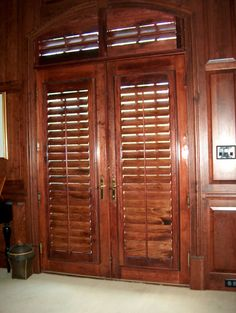 Stained plantation shutters were custom made for these doors and the transoms. The stain was matched to the paneling in the living room for a rich look! Southern Accents, Windows, Remodel, Tall Cabinet Storage, Home Decor, Storage, Paneling, Window Treatments, Shutters