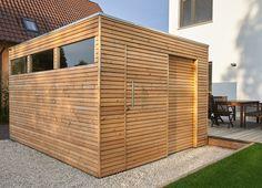 Design Gartenhaus mit Lärchenholz und Schiebetür als Flachdach mit Kubusform und Lichtausschnitt