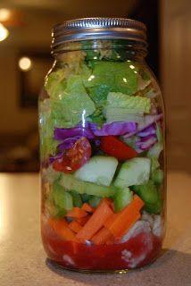 Bottom to top: Raspberry Vinaigrette, chicken, carrot, green pepper, celery, cucumber, tomato, purple cabbage, romaine, cheddar cheese, sunflower seeds