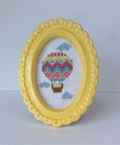 Colorful hot air balloon with clouds completed cross stitch in a small resin frame.  --The Deets- This cross stitch features a colorful hot air balloon among a few clouds. Cross stitched on a white aida cloth. The frame is approximately 3 x 4 inch oval light yellow resin filigree frame and has an easel back to display on a table top.  --Shipping-- I ship USPS First Class and you will receive a tracking number. Each cross stitch will be hand stitched to order in 1-3 days. Orders of multiple…