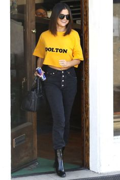 Selena Gomez pairs high waisted jeans with a crop top and patent boots for a summer look on the go.