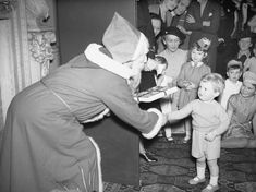 Father Christmas presenting Winston Churchill's grandson with a gift at a Christmas party for Allied naval officers children 1942.