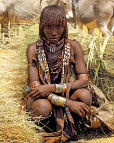 Duka, a married Hamar woman, trades dry grass at a weekly Hamar market in the remote Southern Nations, Nationalities and Peoples Region of southern Ethiopia. Adorned with cowrie-shell collar, copper and brass bracelets, beaded goatskin clothing and iron marital torques. Upper torque with phallic protrusion is wrapped in leather, signifing first-wife status.  Hamar Aesthetics III by david schweitzer Flickr