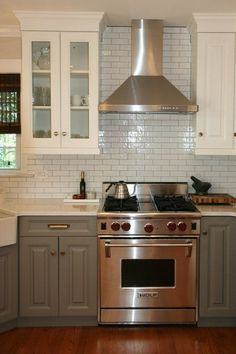love the range, range hood, two-tone cabinets... basically everything! (upper and lower different finishes, glass front uppers)