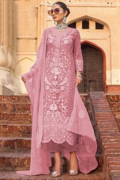 Cast a spell with this Pink Net Trouser Suit Which will surely tell them that the diamonds aren't the only beautiful thing which they have seen. This V neck and Quarter Sleeves Party Wear Attire highlighted with stone, sequins and dori work.  Along with Santoon Trouser in Pink Color with Pink Net Dupatta. Dupatta highlighted with Stone, Sequins and Dori Work.  This Trouser Suit can be customised up to 44 Inches around the Bust.