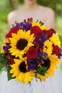 country wedding flowers, sunflower bridal bouquet. blooms like roses and sunflowers, statice, roses and hypericum berries in colors like red, purple and yellows make a beautiful fall wedding bouquet Sunflower Sunsets by Enchanted Florist in Taos, New Mexico. http://www.taosflorist.com/weddings/taos-wedding-flowers/