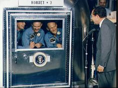 President Richard M. Nixon welcomes the Apollo 11 astronauts aboard the U.S.S. Hornet. Already confined to the Mobile Quarantine Facility are (left to right) Neil A. Armstrong, Michael Collins, and Edwin E. Aldrin Jr.. (July 24, 1969).