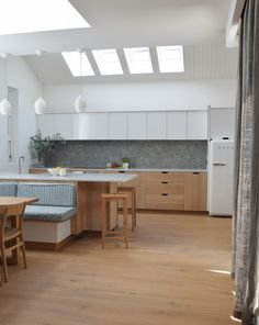 White, oiled oak, handle-less cabinetry with splash back tiles from Fired Earth, delivers a contemporary yet cosy feel to this seaside cottage is Dorset.  The island cleverly defines the kitchen and dining area in this open plan interior where space is fairly limited.  The work tops, by Landford, are Teltos Cararra Onyx and the island houses a white farmhouse sink and Quooker tap. A Fisher and Paykel extractor hood discretely hides beneath the over head cupboards. Country Kitchens, Home Kitchens, Dining Area, Kitchen Dining, White Farmhouse Sink, Extractor Hood, Fired Earth, Work Tops, Cupboards