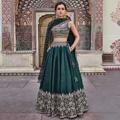 Beautifully embroidered with our signature craft Gota Patti, the Vatsala Lehenga sparkles with every step you take. The emerald green silk lehenga is perfect for any royal occasion. Style Tip: Pair this beautiful lehenga with jadau chand b Indian Gowns Dresses, Indian Fashion Dresses, Indian Designer Outfits, Designer Dresses, Indian Designers, Designer Wear, Indian Lehenga, Green Lehenga, Raw Silk Lehenga