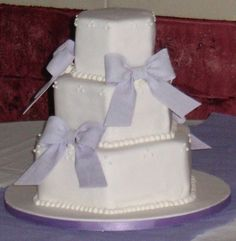"""This is a hexagon shaped cake. The tiers are 6"""", 9"""", and 12"""". The lavender bows are made out of gumpaste and there are swiss dots at the top of each tier."""