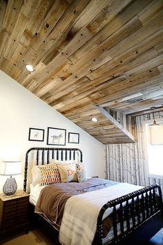source: Utah Valley Parade of Homes Fun boy's bedroom with wood plank sloped ceiling punctuated with pot lighting over black spool bed filled with light gray blanket, brown blanket and colorful pillows next to single wood nightstand with black string lamp. Boy's bedroom features framed animal prints over black spool bed and Cole & Sons Woods Wallpaper accent wall.