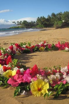 Tropical flowers form a sacred ceremony space on the beach.