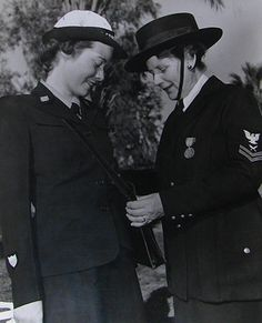 At right, Mrs. Sadie Flay, a WWI Yeomanette, compares her uniform with that of a SPARs' from 1943. The Coast Guard SPAR is Lons McLellan.
