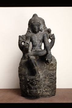 """Shiva Dakshinamurti (Figure). Thanjavur, India.late 12th century.Daksinamurti, the """"Lord who faces South"""",represents Siva as the supreme teacher of yoga, music, jnana (divine knowledge) and all the arts and sciences.This image, with a rosary and flame in the upper hands, is Vyakhyanamurti, Siva as the expounder of the sastras. Four-armed Siva is depicted with the uncut hair of an ascetic, seated in the virasana (heroic) posture,the lower right hand raised in the gesture of teaching in…"""