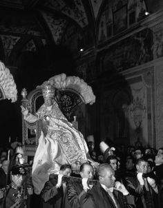 Pope Pius XII is carried in his sedia gestatoria through the Sala Ducale on the anniversary of his coronation as pope. His hand is raised in blessing.    Most of these symbols of the Papacy have been abolished.