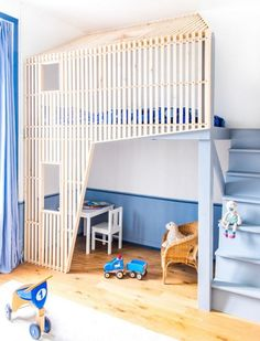 LOFT BED - To make a little room for her younger  sister in her bedroom, the Marius bed had to be lofted. They used a custom-built house in house design, painted in blue tolddsaa match the colors of the room (curtains, wainscoting). Closets were placed under the stairs to save space.
