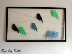 DIY Birds on a Wire: Cut out bird silhouettes from cardstock, tape paperclips on the backs, and attach birds to silver thread stapled to a frame.