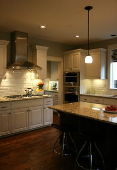 Dark hardwood floors, accent dark island, granite tops, white cabinets, subway tile, stainless appliances. Love this