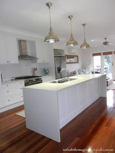 Like ours, has floorboards, white cabinetry, stainless steel appliances and matching pendant lights and lots of light