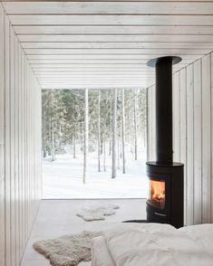 Necessities.~Four-Cornered Villa, Avanto Architects, white wood floor to ceiling interior, black wood-burning fireplace, deer skins on floor, edge to edge plate glass windows